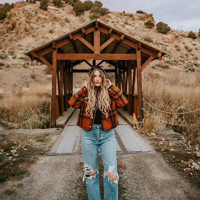 girl with long dirty blonde hair posing in front of a bridge in idaho